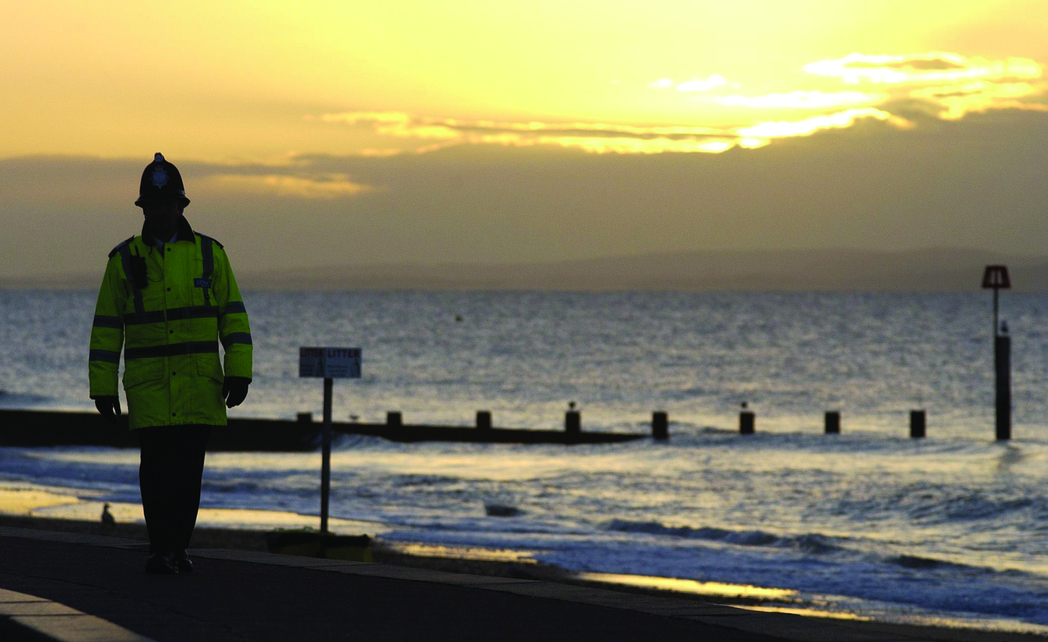 Police officer walking down a beach