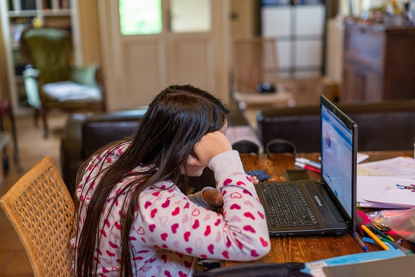 A young girl is sat alone at a table with a laptop